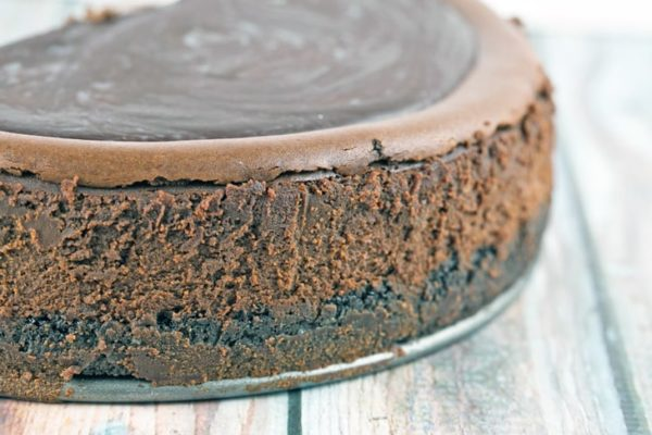 side view of a dark chocolate cheesecake showing the oreo crust, chocolate cheesecake, and chocolate ganache topping
