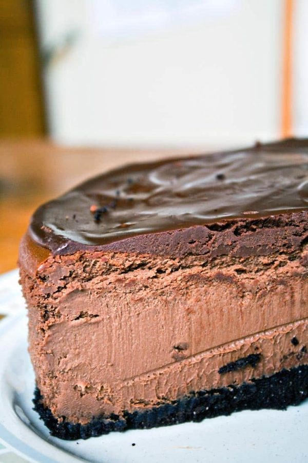 a cut slice of dark chocolate cheesecake showing the smooth, creamy, chocolate interior
