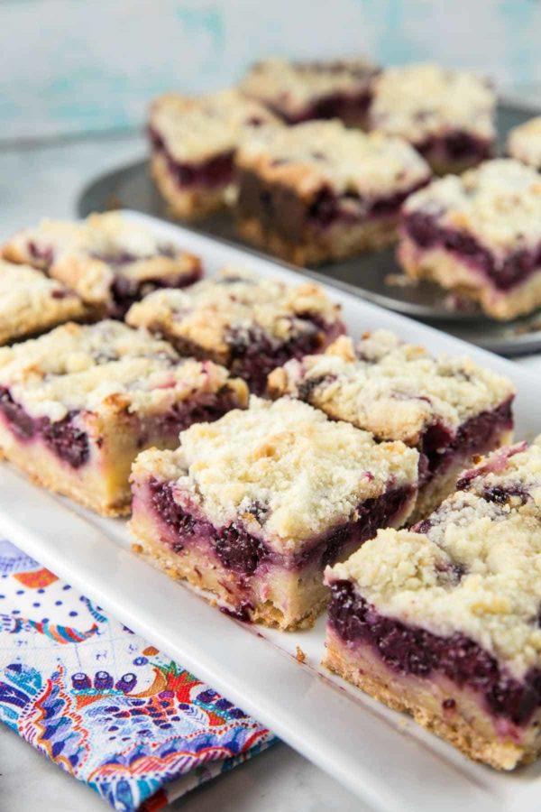 eight blackberry pie bars arranged on a rectangular serving plate