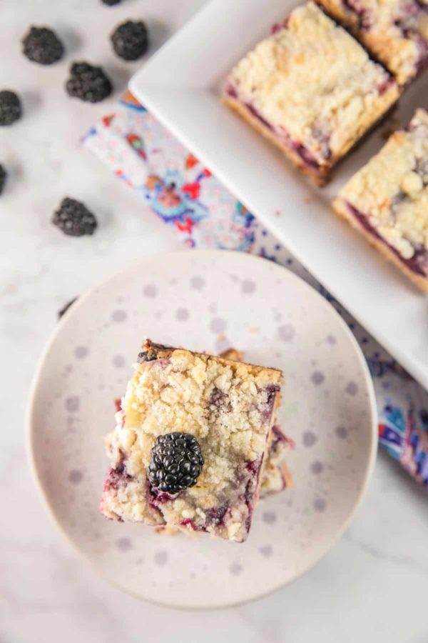 a stack of blackberry pie bars on a speckled plate with blackberries scattered in the background