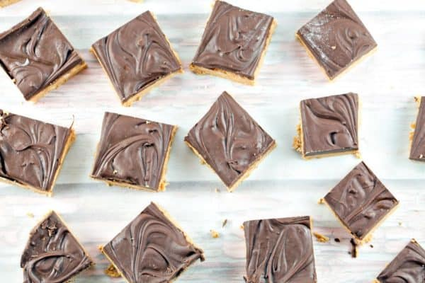 squares of peanut butter bars arranged on a piece of parchment paper