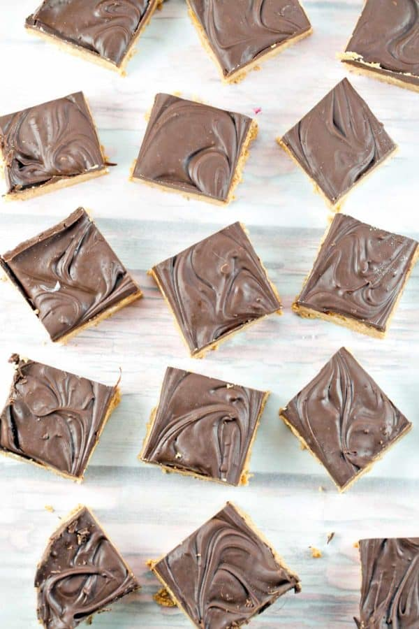 squares of five ingredient peanut butter bars covered with swirls of melted chocolate
