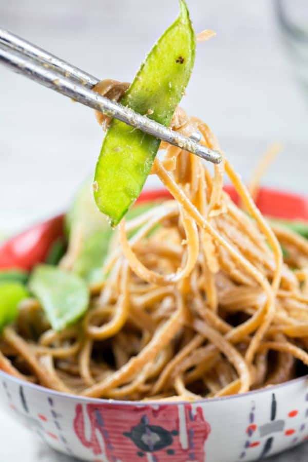 a snow pea and noodles covered in a thai peanut sauce held by chopsticks above a large bowl