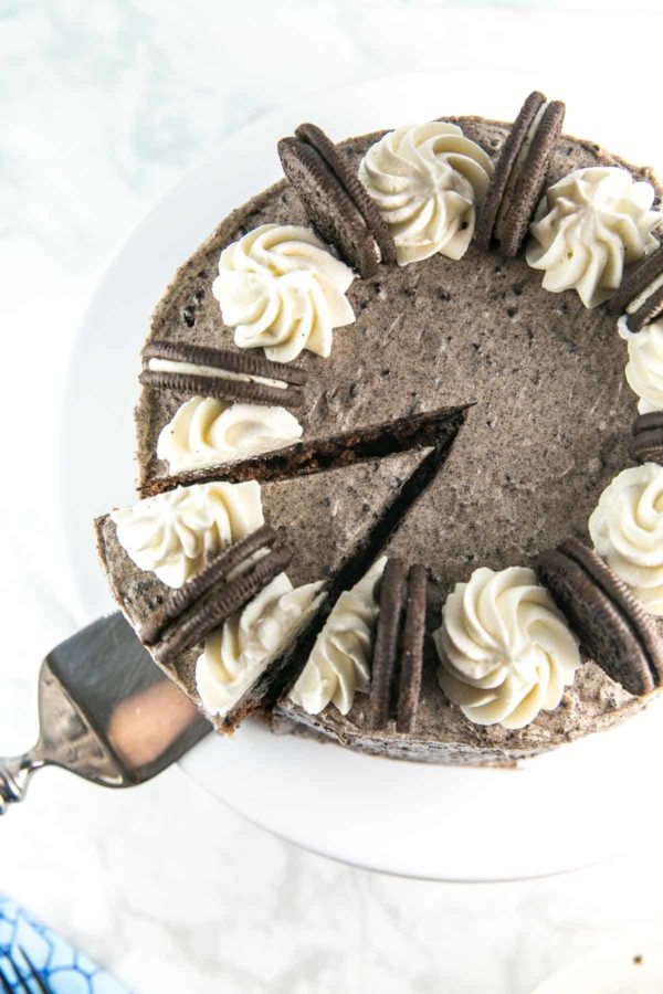 overhead view of a spatula about to remove one cut slice from a chocolate oreo cake