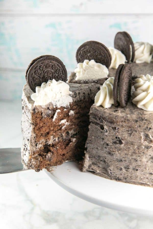 one slice of chocolate oreo cake being removed from an entire layer cake on a cake server, showing the rich chocolatey interior and the fluffy oreo cream cheese frosting