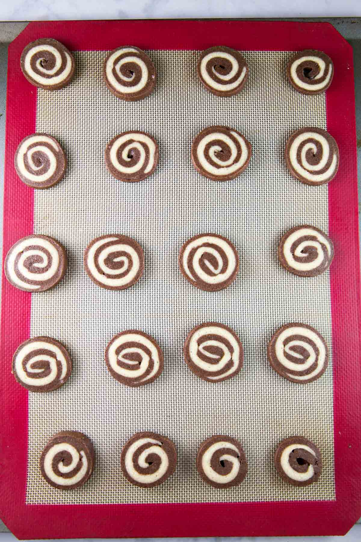 chocolate pinwheel cookies arranged in rows on a baking sheet