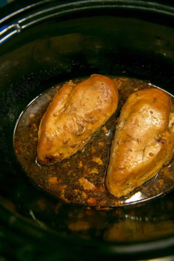 two chicken breasts in a slow cooker