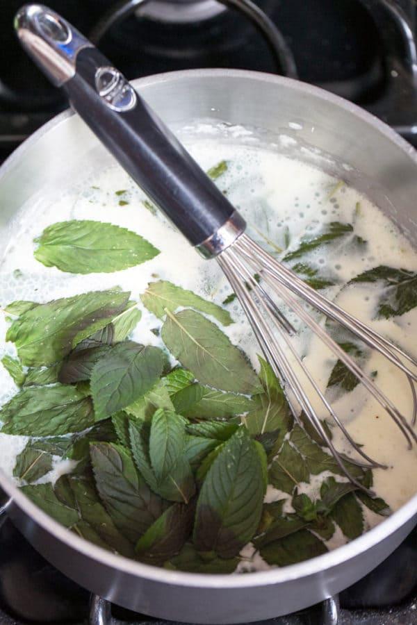 mint leaves seeping in warm milk in a sauce pan