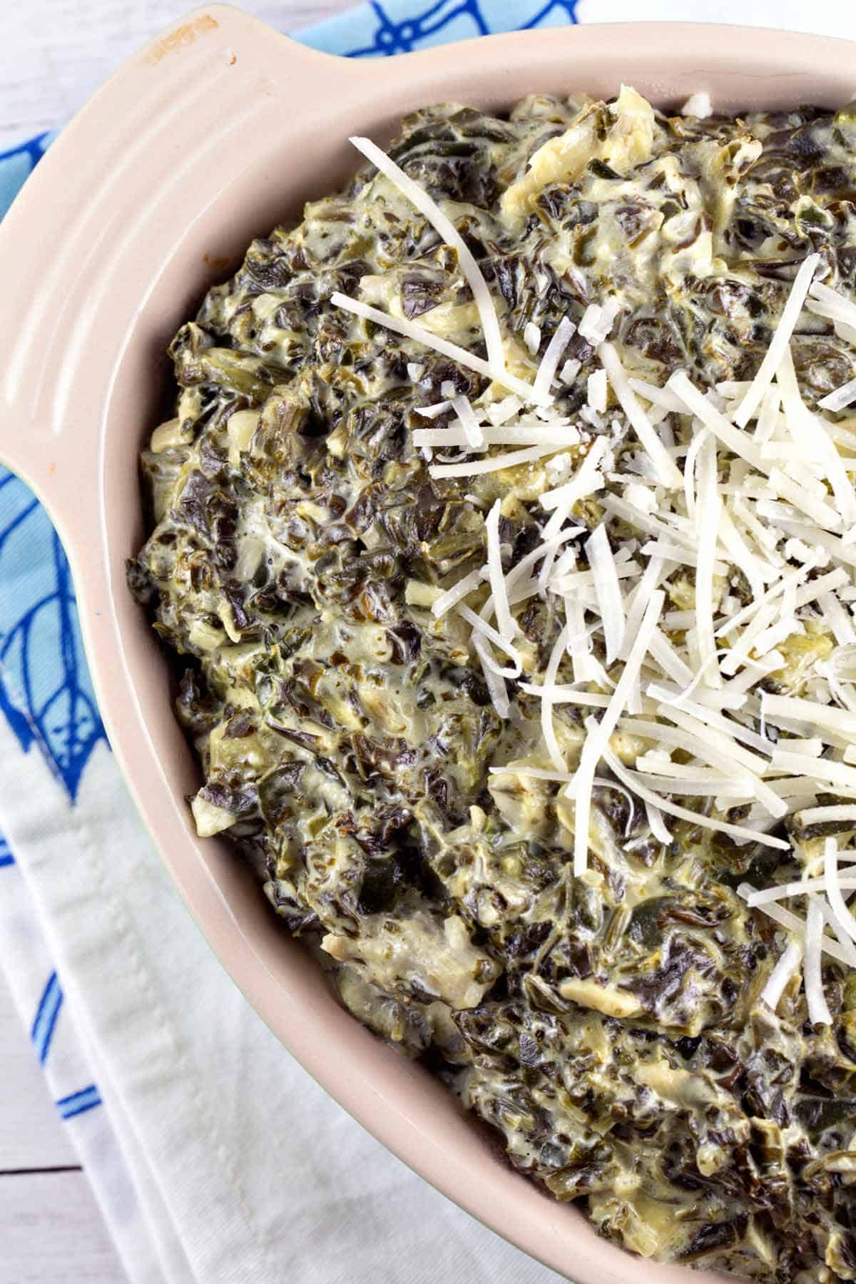 ceramic bowl filled with baked spinach and artichoke dip
