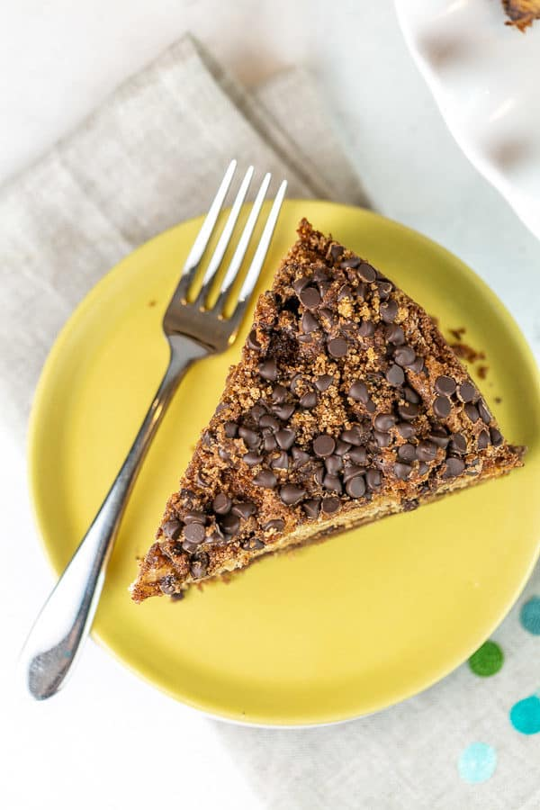 slice of cake on a yellow plate highlighting the chocolate chip streusel topping