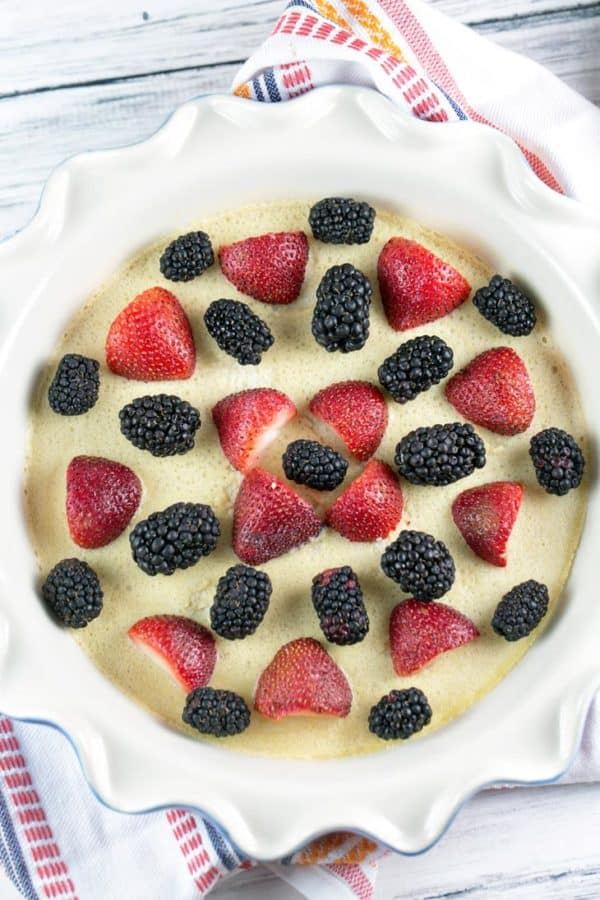 partially baked clafoutis with strawberries and blackberries on top