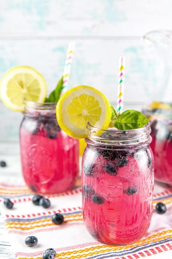 three mason jars filled with blueberry basil bourbon lemonade with wedges of lemon and colorful paper straws