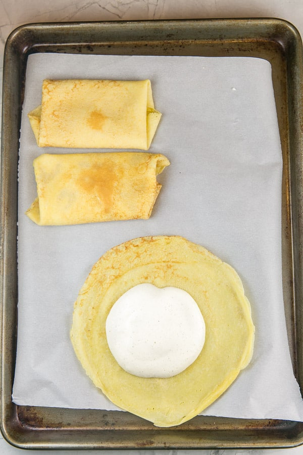 two rolled blintzes on a sheet pan next to a round crepe with a dollop of blintz filling in the center