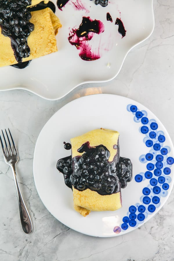 overhead view of a blintz on a blueberry painted plate