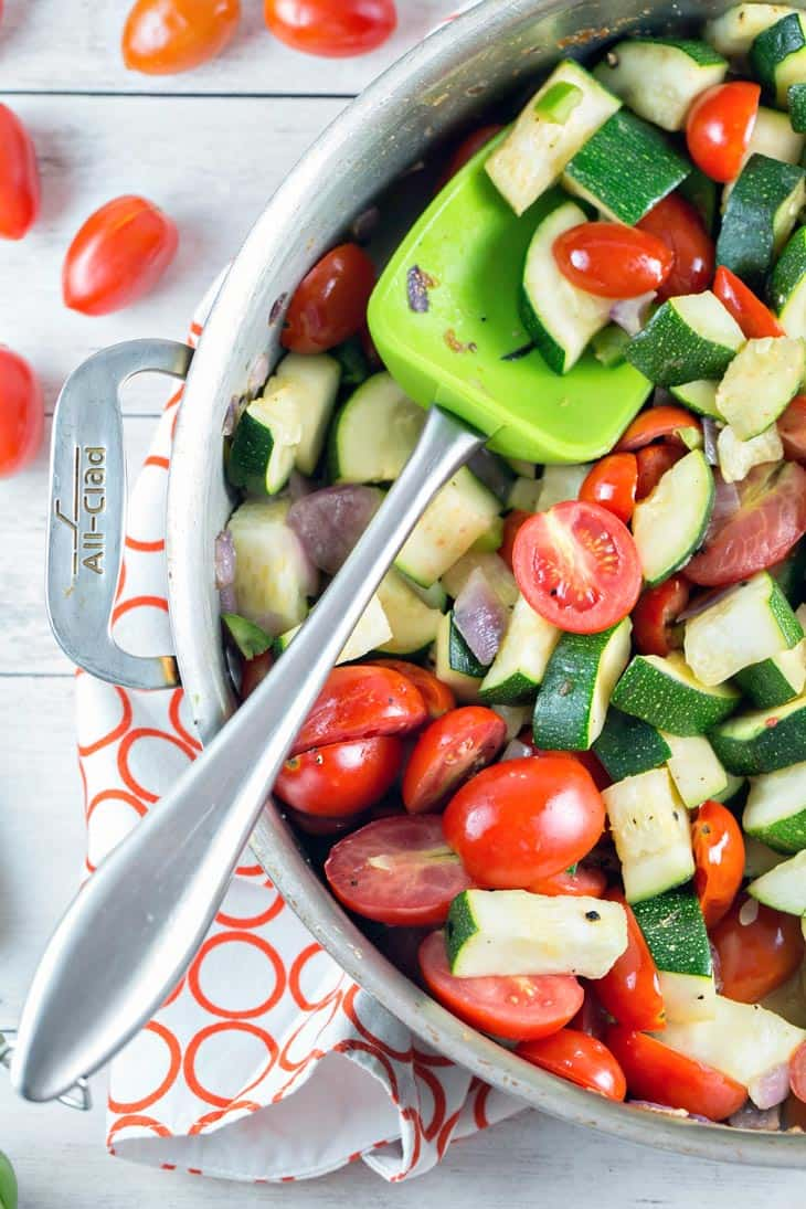 skillet filled with raw zucchini, cherry tomatoes, and red onion