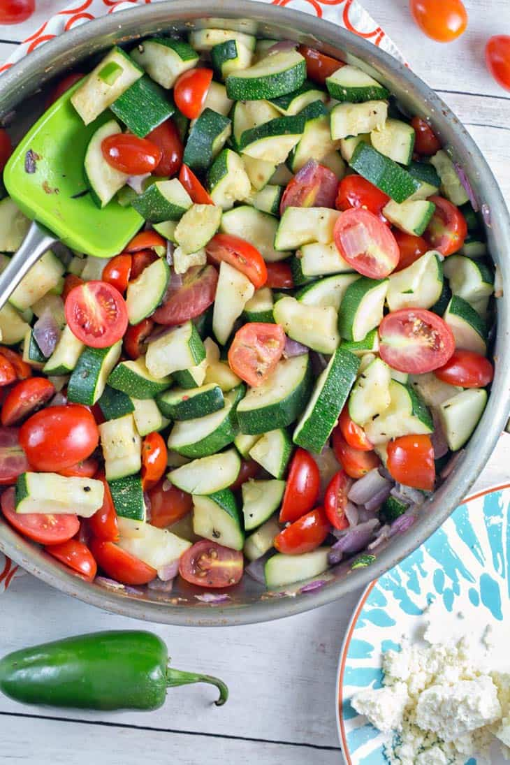 sauteed zucchini, tomatoes, and red onion in a skillet next to a jalapeno pepper and cotija cheese