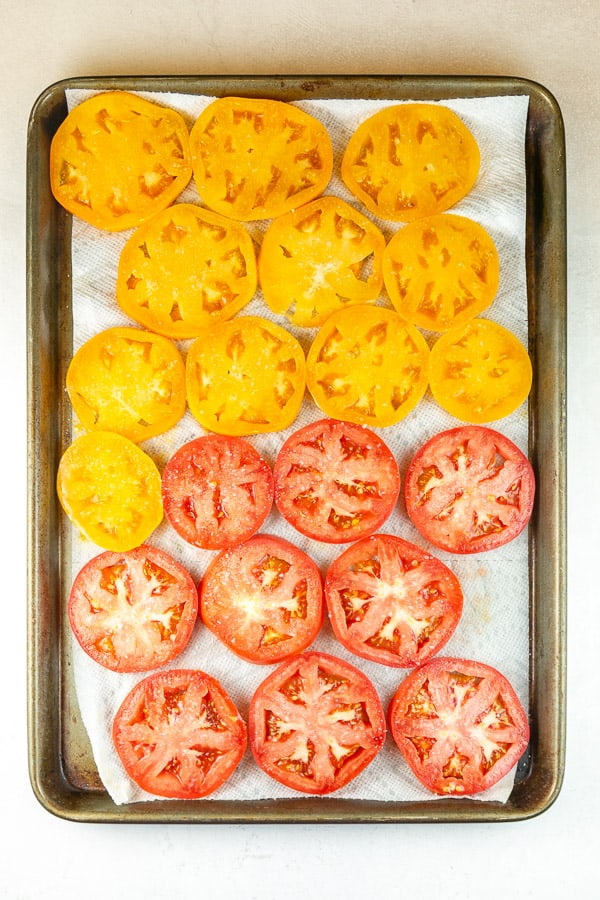 sliced tomatoes on a cookie sheet