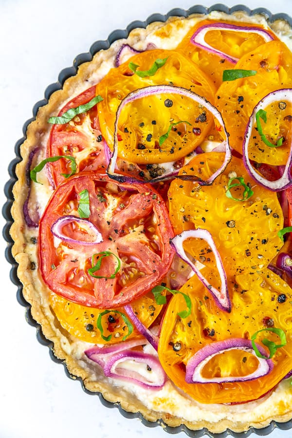 tomato pie showing fresh tomatoes, red onion, and basil baked in a crust