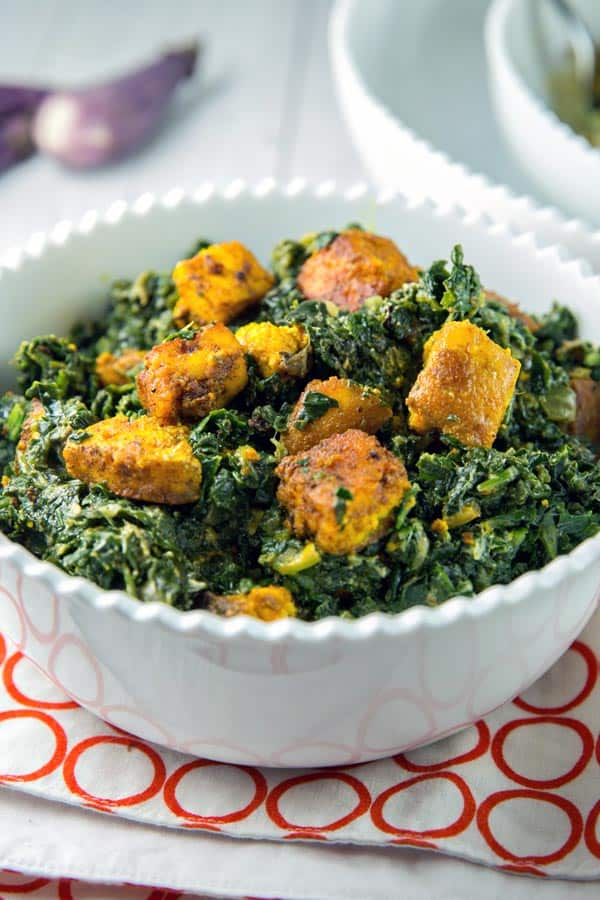 spinach with cubes of sauteed paneer in a white serving bowl
