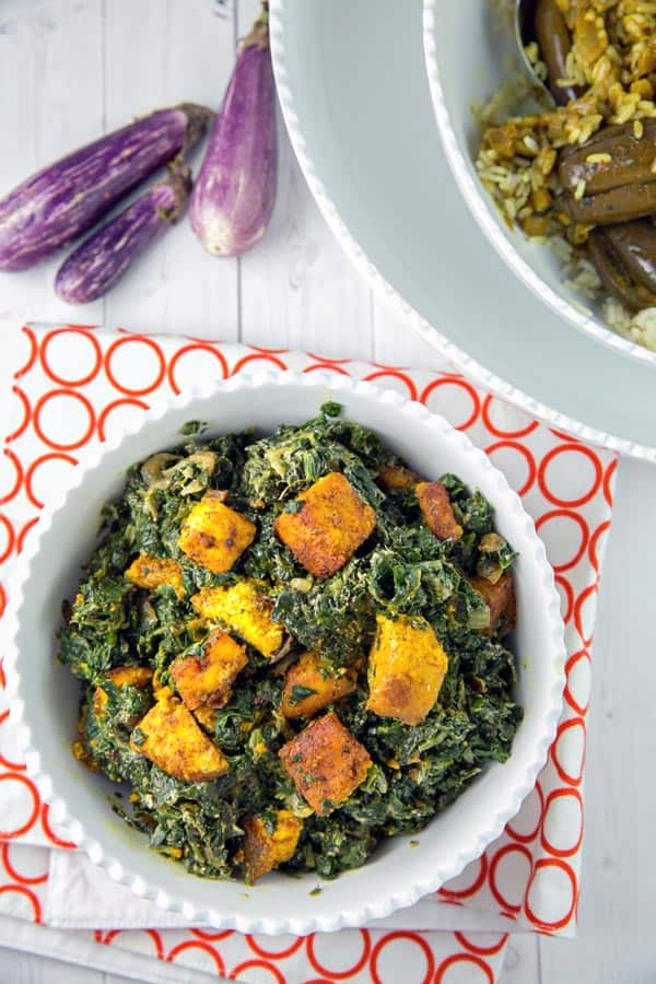 saag paneer in a bowl next to indian eggplant curry