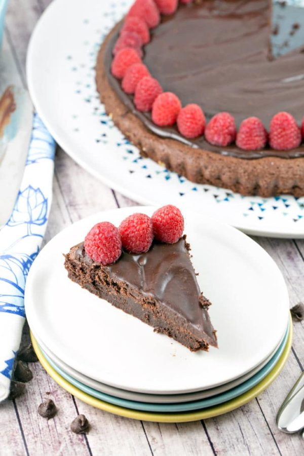 a large cut slice of flourless chocolate cake on a stack of dessert plates with the rest of the cake in the background
