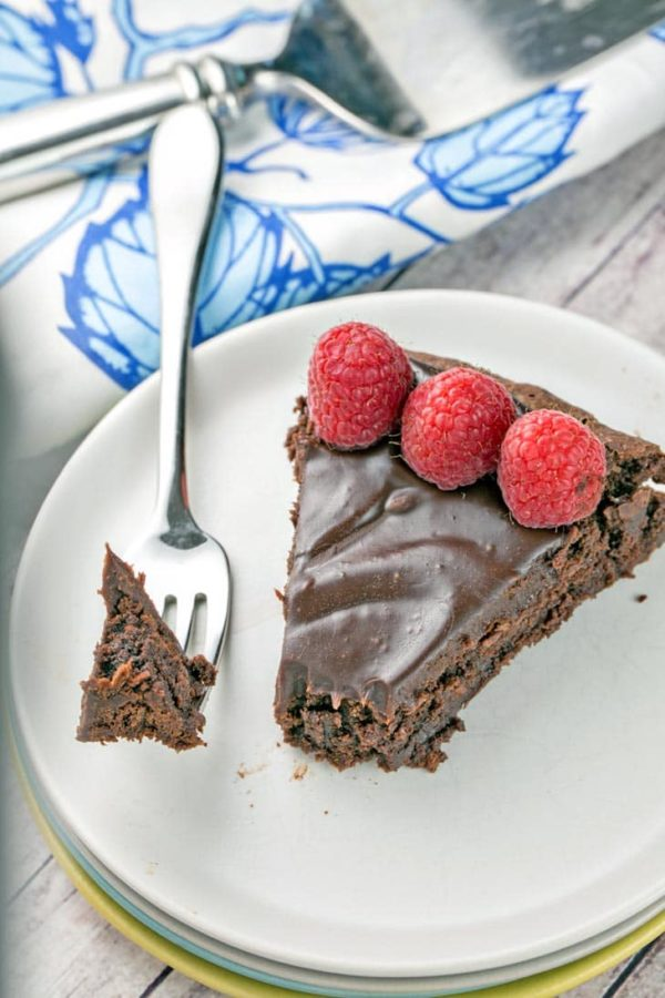 one slice of flourless chocolate cake with chocolate ganache and three raspberries on a dessert plate with a fork holding one bite of cake resting on the edge of the plate
