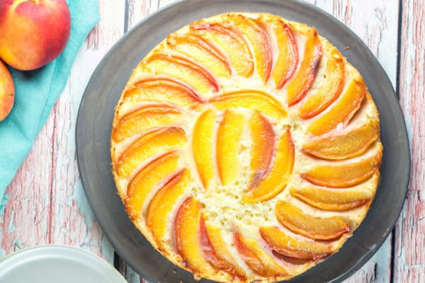 cake on a gray plate covered with a spiral of nectarine slices