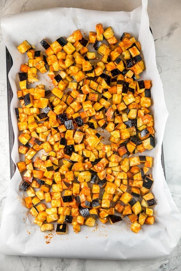 a sheet pan full of honey and paprika covered eggplant cubes before roasting
