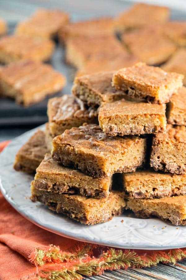 butterscotch blondies stacked tall on a dessert plate with more cut brownies in the background