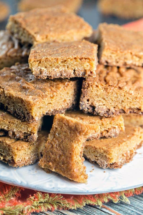 a pile of butterscotch blondies with one blondie with a bite taken out of it