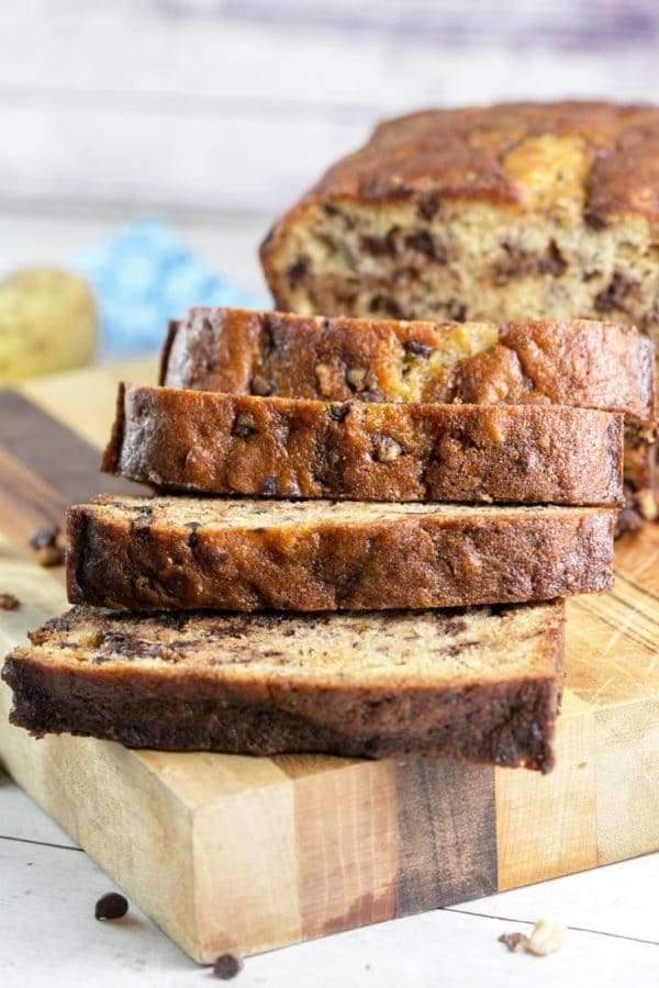 slices of banana bread with chocolate chips and hazelnuts arranged on a wooden cutting board