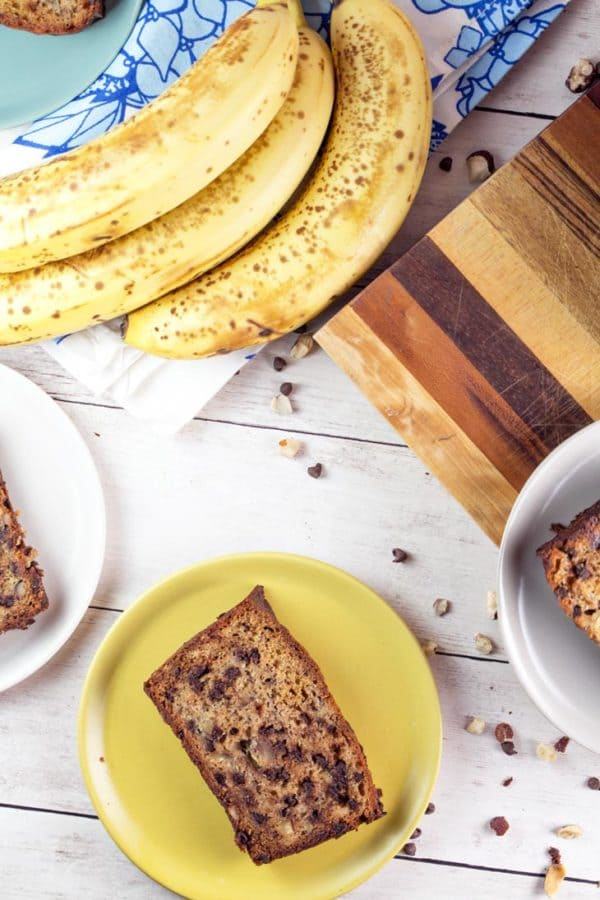 a slice of hazelnut chocolate chip banana bread surrounded by bananas and chopped hazelnuts