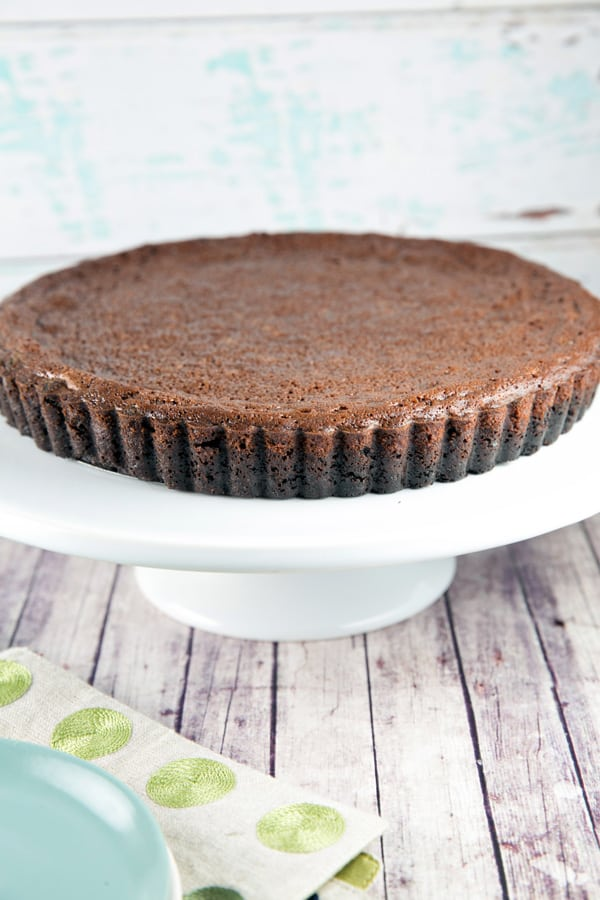 side view of an uncut chocolate buttermilk pie on a white cake plate highlighting the oreo cookie crust