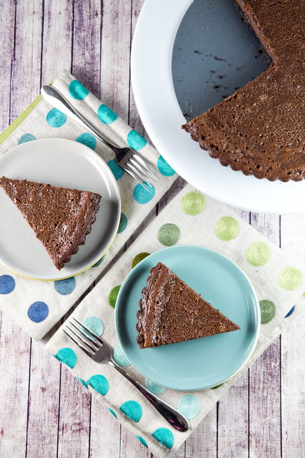 two slices of chocolate buttermilk pie on decorative dessert plates and polka dot placemats