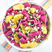 Thinly sliced watermelon radish paired with winter citrus, candied walnuts, and tangy goat cheese are the perfect compliment to a simple spinach salad.