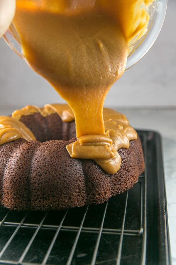 peanut butter ganache flowing from a mixing bowl onto a chocolate bundt cake