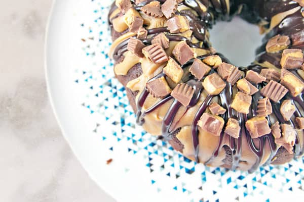 overhead view of a chocolate peanut butter cup bundt cake covered in chopped reeses peanut butter cups