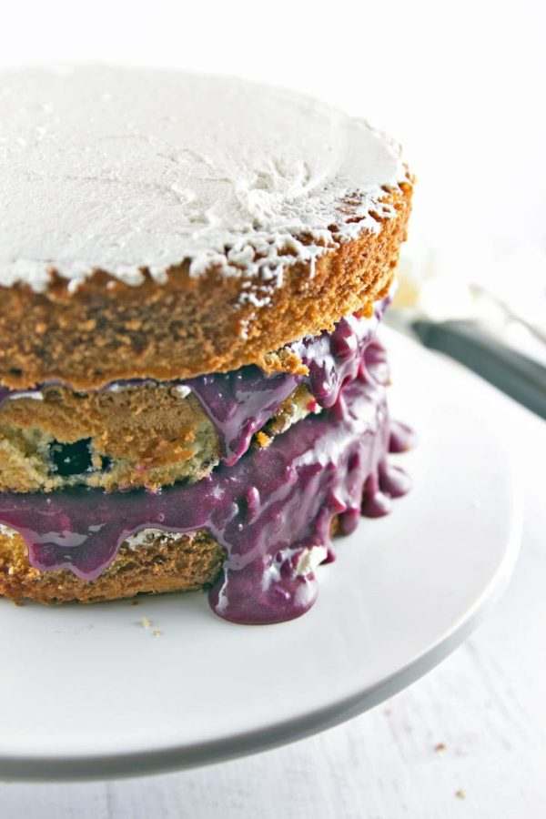 three layers of vanilla cake with thick purple blueberry curd spilling out around the outside of the cake