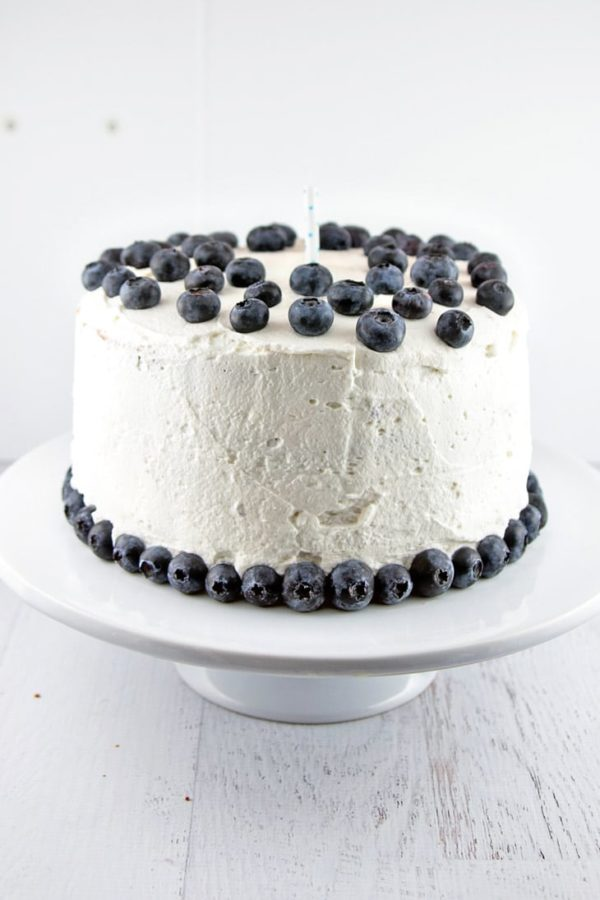 a three layer vanilla cake filled with blueberry cardamom curd covered in white whipped cream frosting and decorated with blueberries