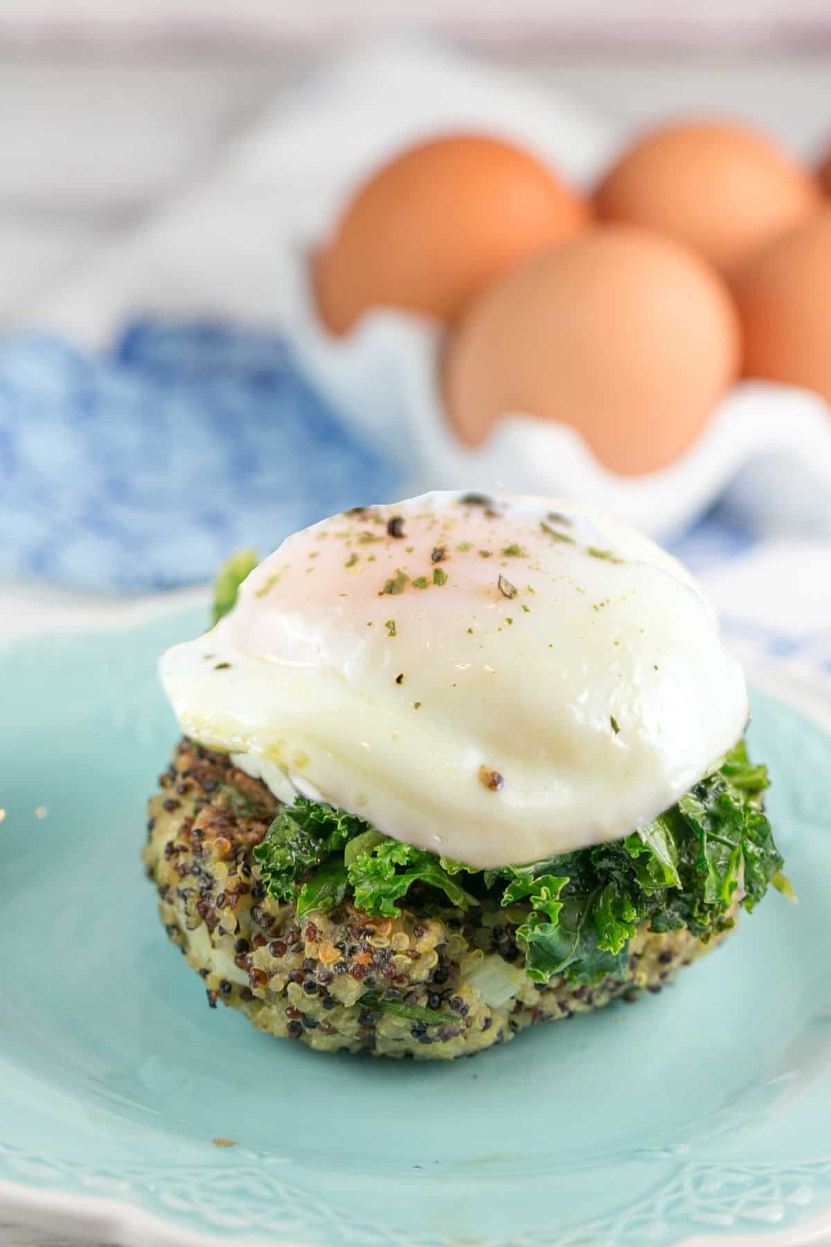 side view of a tricolored quinoa cake covered in kale and a poached egg on a blue plate