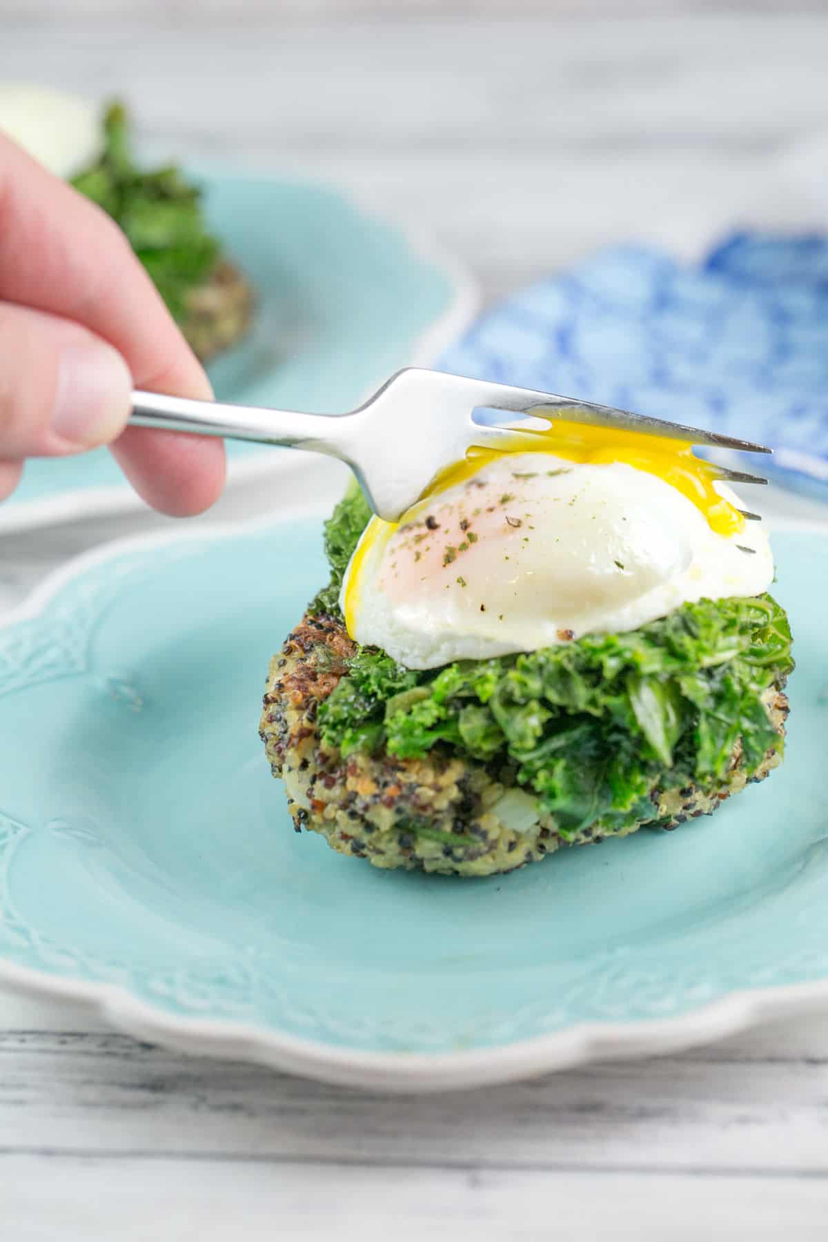 side view of a quinoa cake topped with a poached egg with a fork breaking open the egg