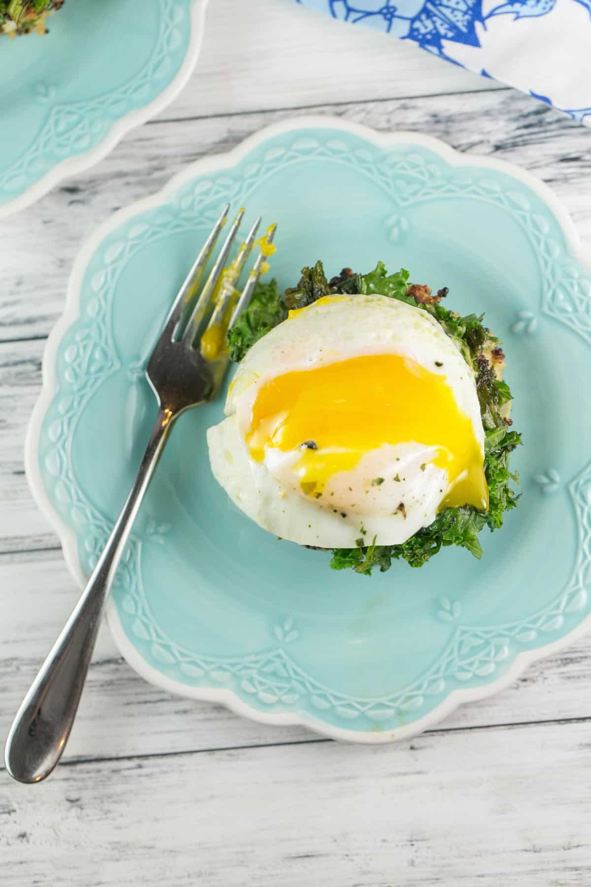 overhead picture of a poached egg with the yolk dripping over kale and a quinoa cake