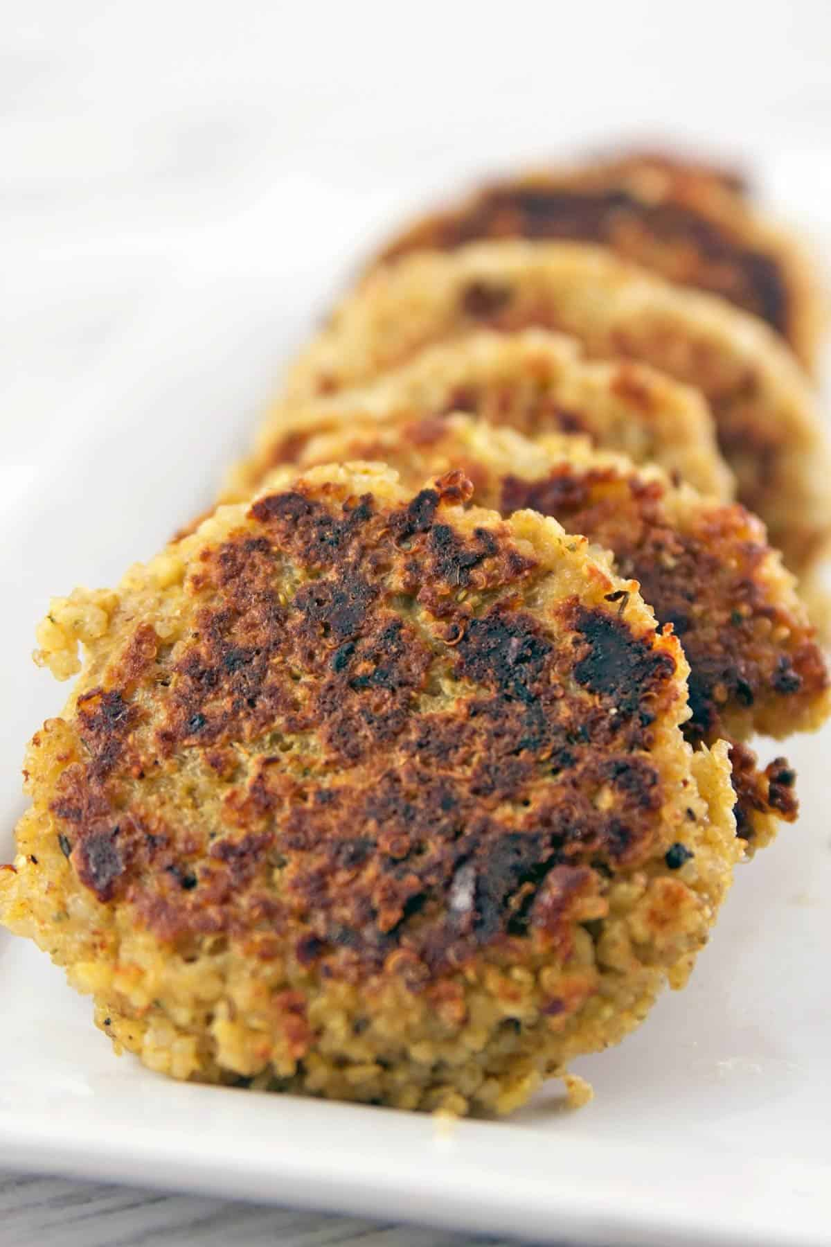 cooked quinoa cakes stacked on a white rectangular serving plate