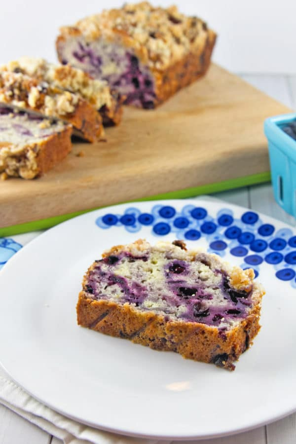 a slice of blueberry pie quick bread on a plate with the rest of the sliced loaf in the background