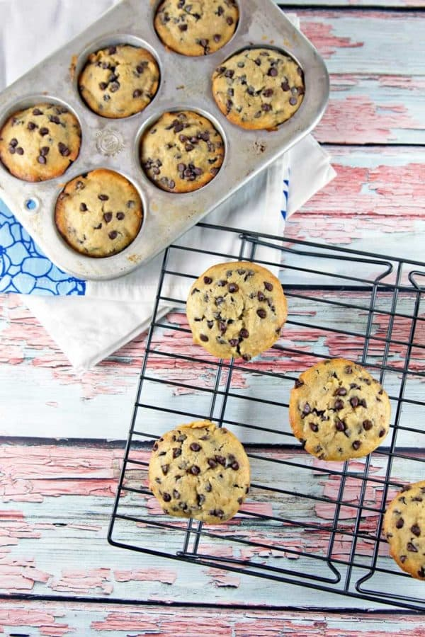 chocolate chip banana bread muffins in a muffin tin and on a cooling rack