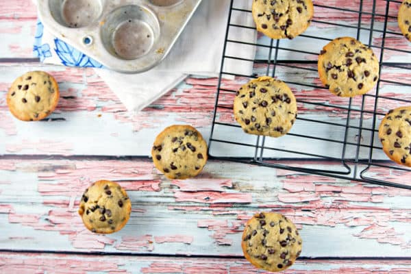 chocolate chip banana bread muffins on a wooden table and cooling rack