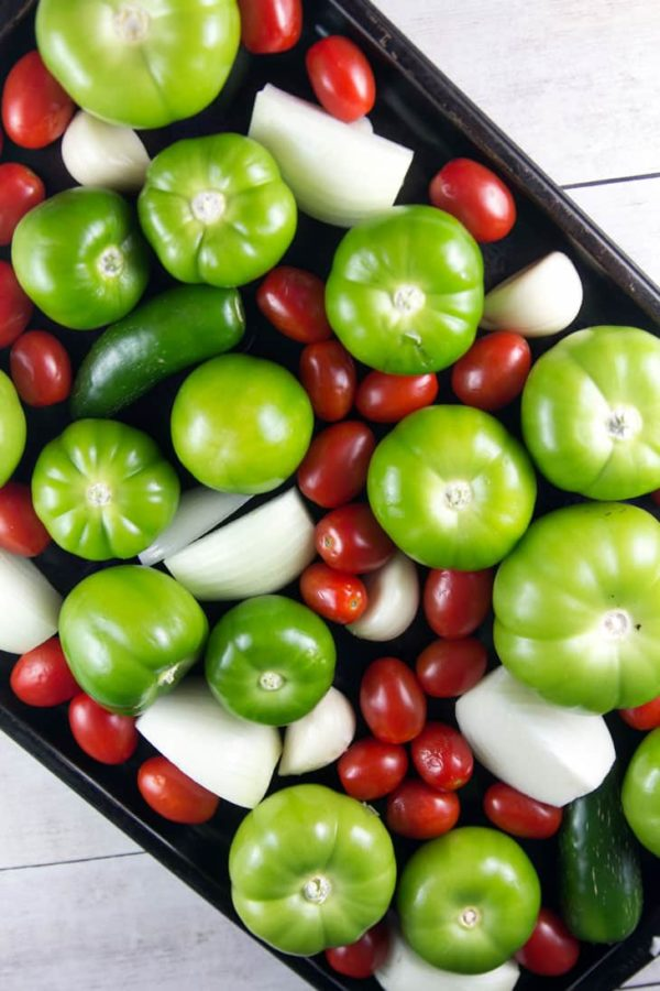 a sheet pan with fresh tomatillos, cherry tomatoes, onions, and peppers which will turn into salsa verde