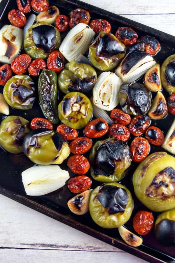 a sheet pan filled with roasted and charred tomatillos, cherry tomatoes, onions, and jalapenos