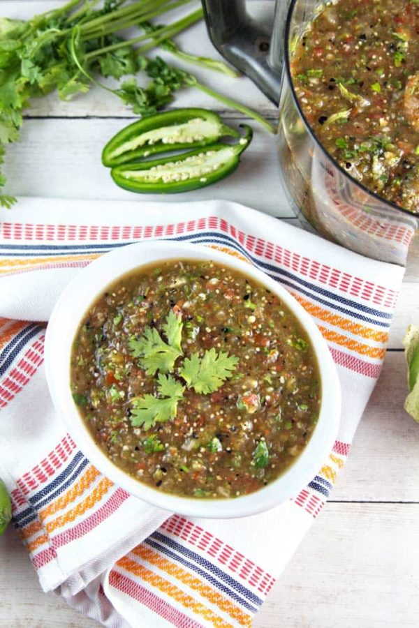 homemade roasted tomatillo salsa verde in a white serving dish on a colorful dishtowel