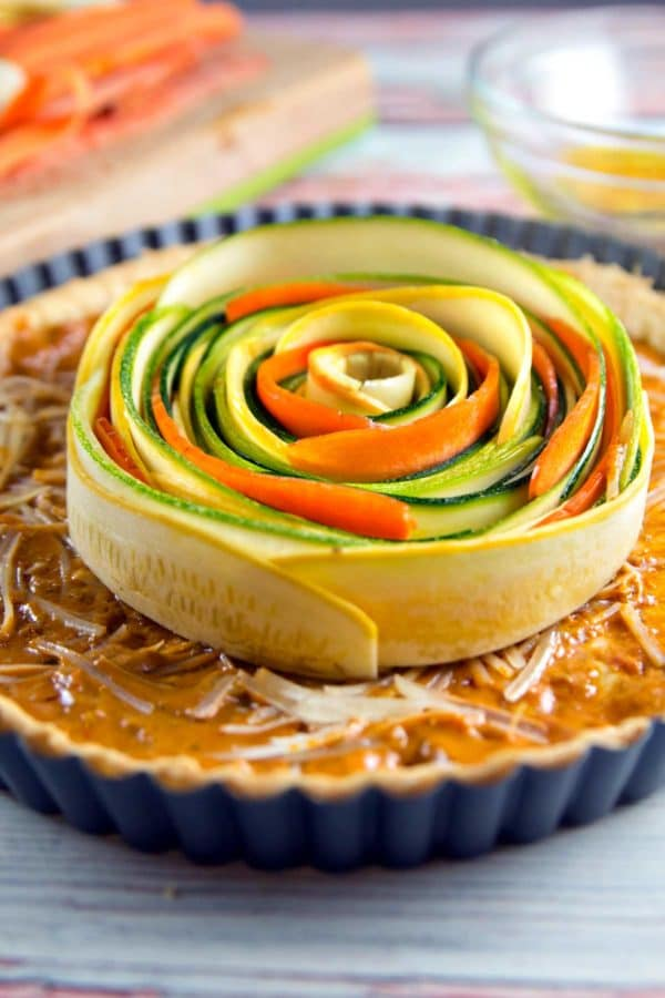 thinly sliced vegetables starting to form a spiral pattern in the center of a pie crust spread with sundried tomato pesto